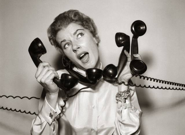 1950s 1960s Overwhelmed Stressed Woman Answering Four Black Telephone Phone Receivers At One Time